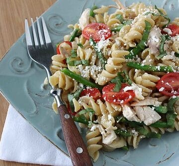 Basil chicken pasta salad on a blue plate with a wood handled fork.