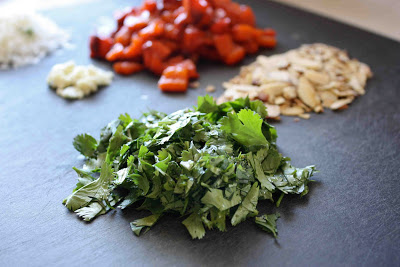 Chopped cilantro, roasted peppers and almonds on a black cutting board.