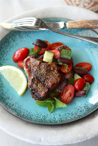These grilled lamb chops are simply prepared and topped with squeeze of lemon and a fresh salad of tomatoes, cucumbers and kalamata olives. 266 calories and 6 Weight Watchers Freestyle SP #wwfreestyle #lamb