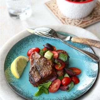 These grilled lamb chops are simply prepared and topped with squeeze of lemon and a fresh salad of tomatoes, cucumbers and kalamata olives. 266 calories and 6 Weight Watchers Freestyle SP #lambrecipes #grillingrecipes