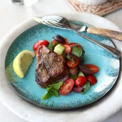 Grilled lamb chop on blue plate, topped with salsa.