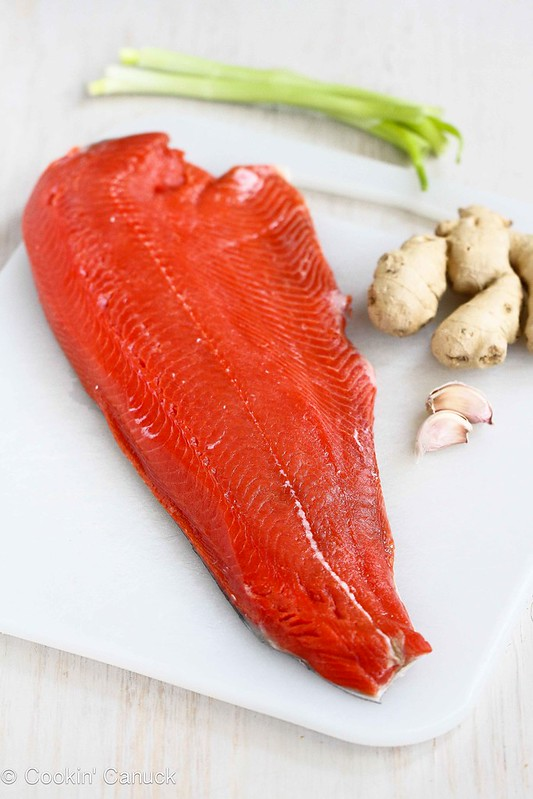 Salmon fillet on a cutting board, with fresh ginger and garlic.