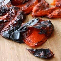Roasted bell peppers on a bamboo cutting board