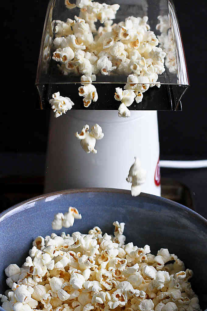 Popcorn popping out of an air popper into a blue ceramic bowl.