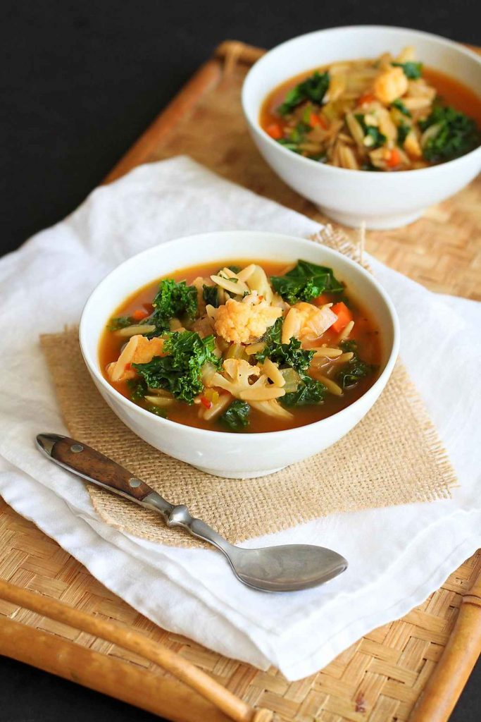 This vegetarian kale soup is packed with orzo and cauliflower. A hearty, healthy recipe for cold weather! 205 calories and 5 Weight Watchers SmartPoints
