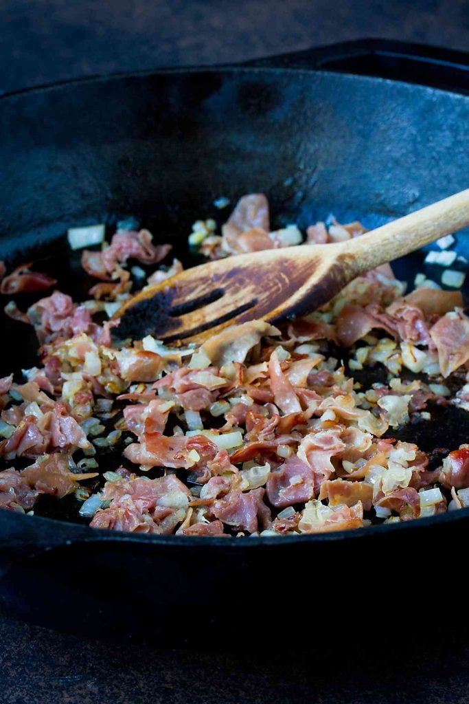 Prosciutto and shallots, sizzling and golden brown in a cast iron skillet.