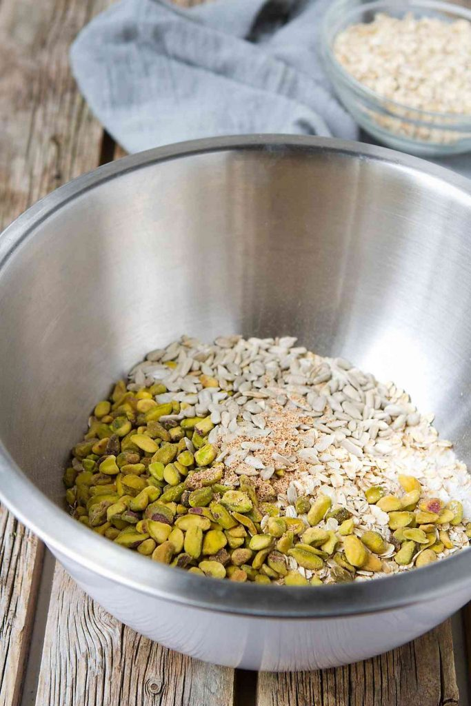 Pistachios, oats and sunflower seeds in mixing bowl.