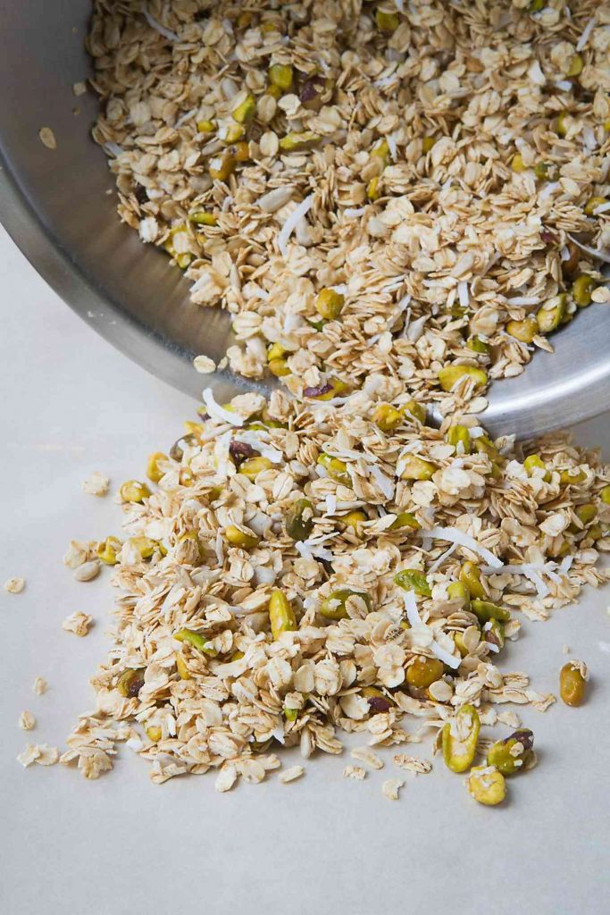 Maple Pistachio Granola pouring onto baking sheet.