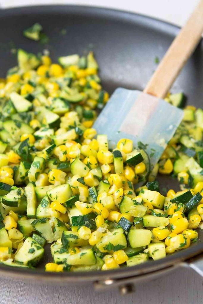 Zucchini, corn, lime and cilantro in a skillet.