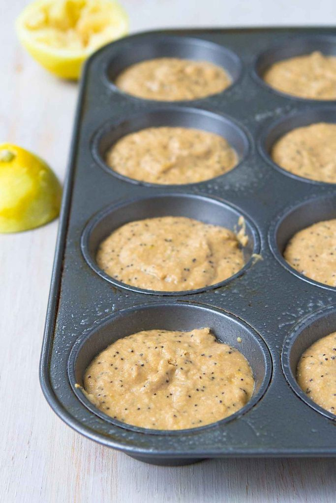Lemon poppy seed muffin batter in a muffin tin, ready to bake.