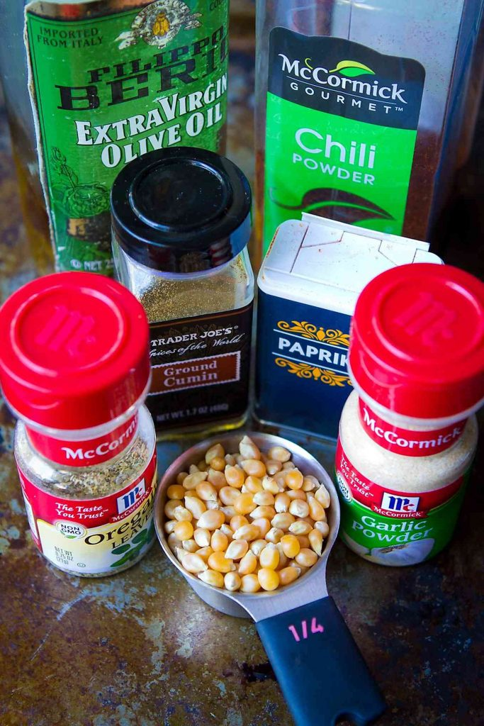 Popcorn and taco seasoning ingredients - olive oil, oregano, chili powder, cumin, paprika and garlic powder.