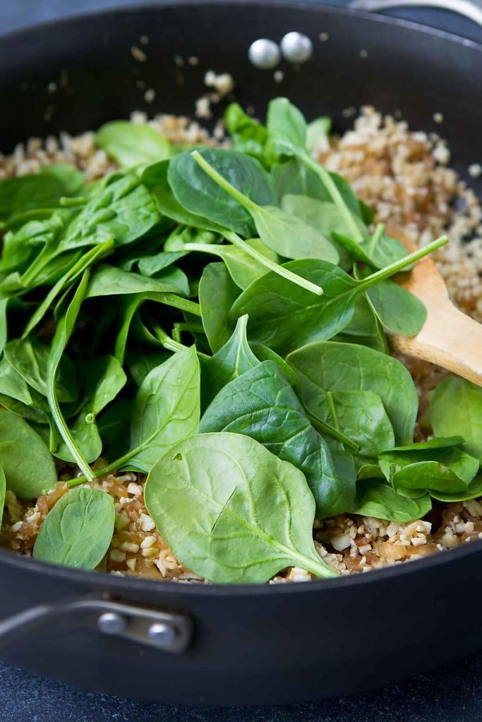 Adding fresh spinach leaves to a skillet full of cauliflower rice and caramelized onions.