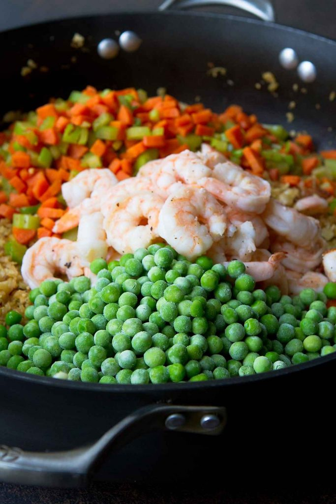 Shrimp, peas, vegetables and cauliflower in a large skillet.