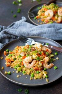 Shrimp and cauliflower fried rice with vegetables on a gray plate.