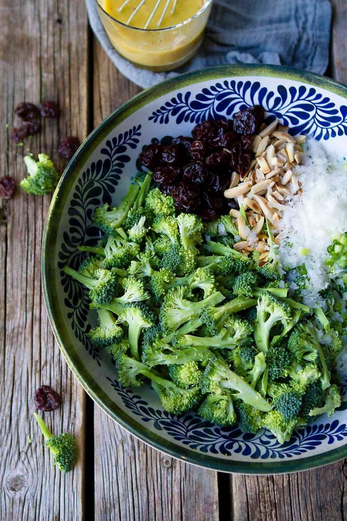 Chopped broccoli, Parmesan cheese, toasted almonds and dried cherries in a serving bowl.