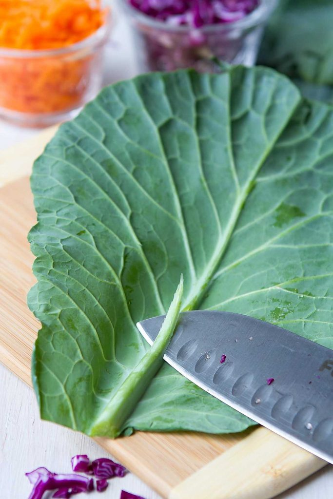 Trimming the stem of a collard green leaf with a sharp knife.