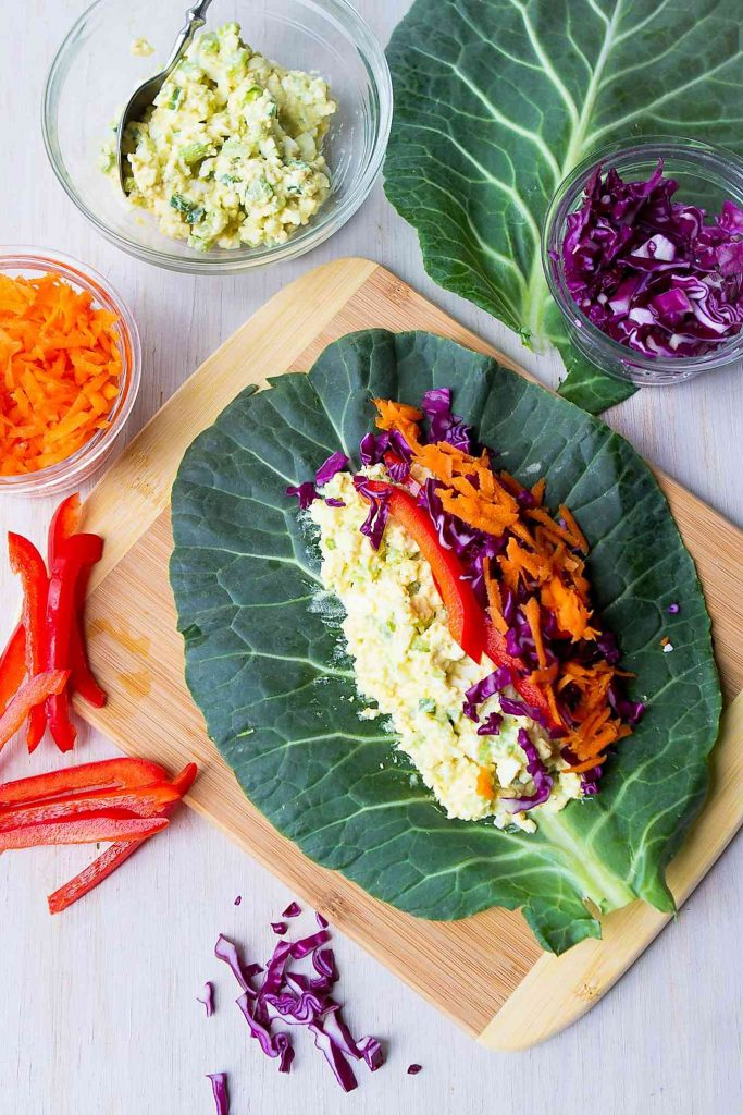 Egg salad, grated carrot and cabbage arranged on a collard green leaf.