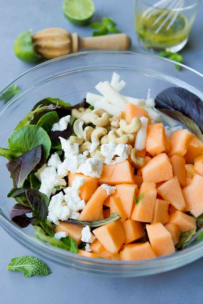 Cantaloupe, goat cheese, lettuce and cashews in a glass bowl.