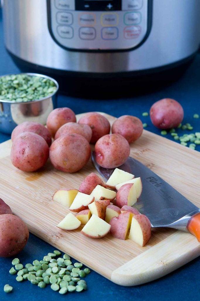 Chopping Creamer potatoes on a cutting board.