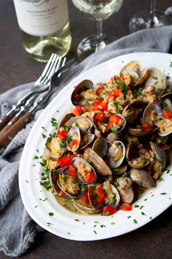 Steamed littleneck clams and sausage on a white plate, with glasses of white wine.