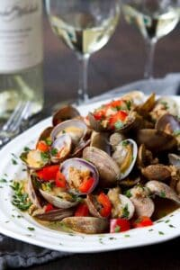Steamed clams, sausage and red pepper in a white bowl, with glasses of wine in background.