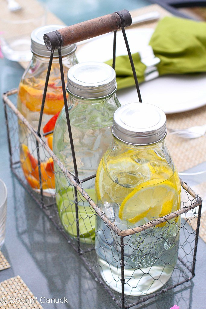 Water carafes with fruit, set up on patio table.