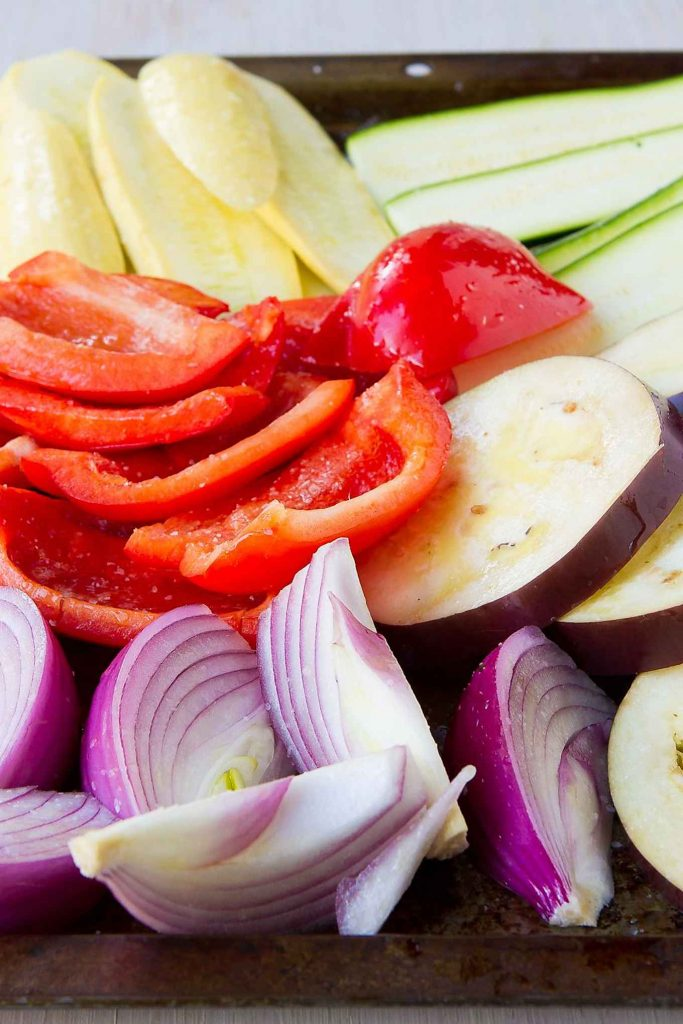 Sliced vegetables - zucchini, yellow squash, red onion, red bell peppers and eggplant - ready for grilling.