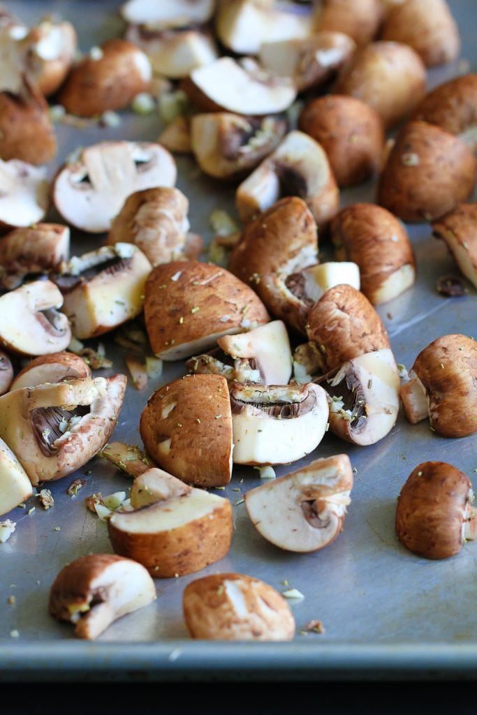 Quartered crimini mushrooms, tossed with olive oil, garlic and rosemary, on a baking sheet.