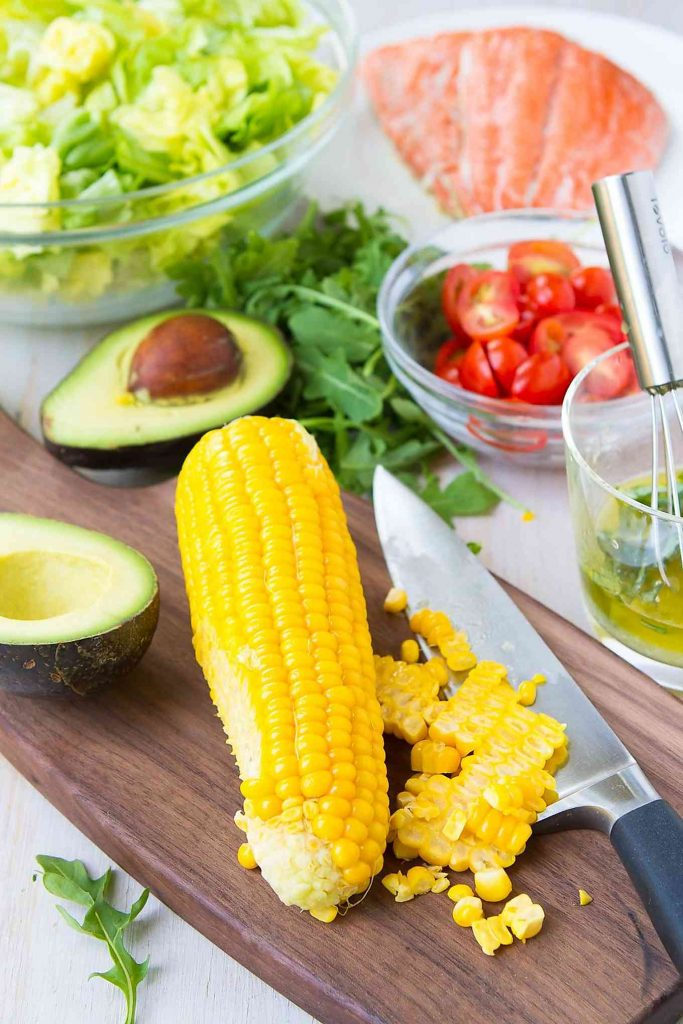 Ingredients for chopped salad: corn, avocado, salmon, lettuce and tomatoes.