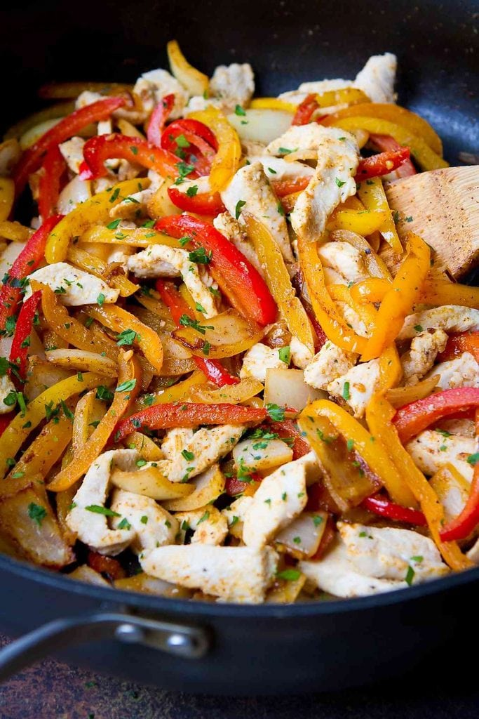 Sauteed chicken breasts and bell pepper strips in a nonstick skillet. Chicken fajitas recipe.