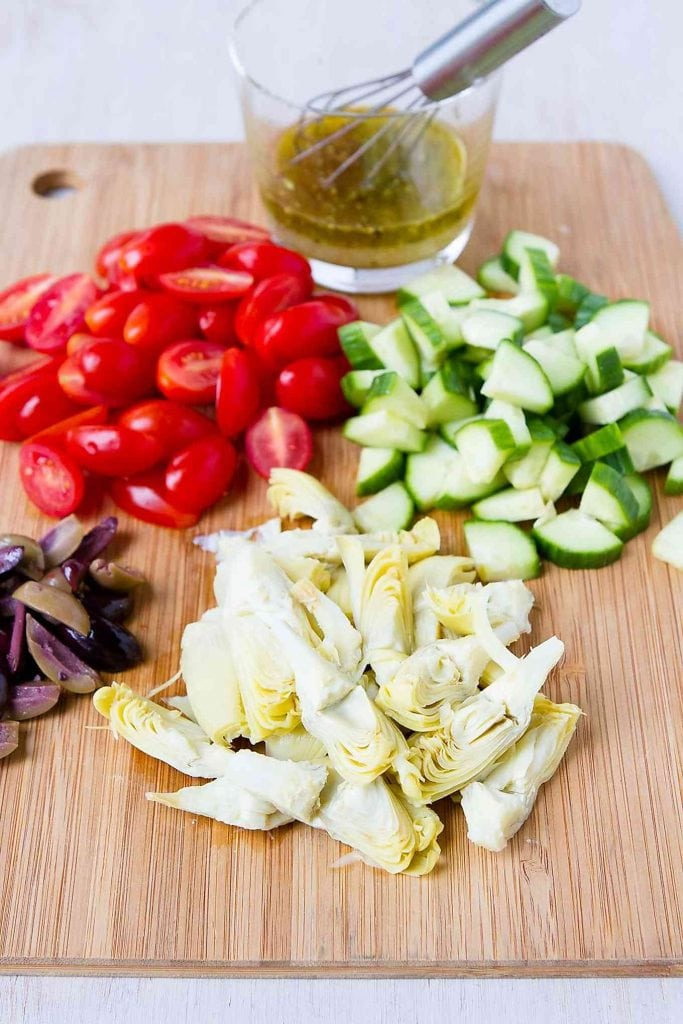 Tomatoes, diced cucumber, artichokes, olives and lemon vinaigrette on a wooden cutting board.