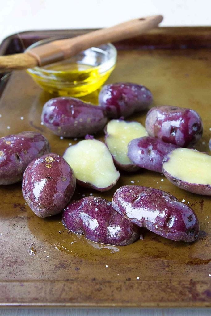 Something Blue potatoes on a baking sheet, tossed with olive oil.