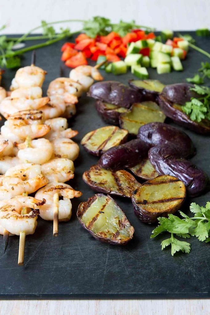 Grilled potatoes and shrimp, diced cucumber and tomatoes on a cutting board.