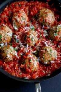 Large turkey meatballs in a skillet with homemade tomato sauce.