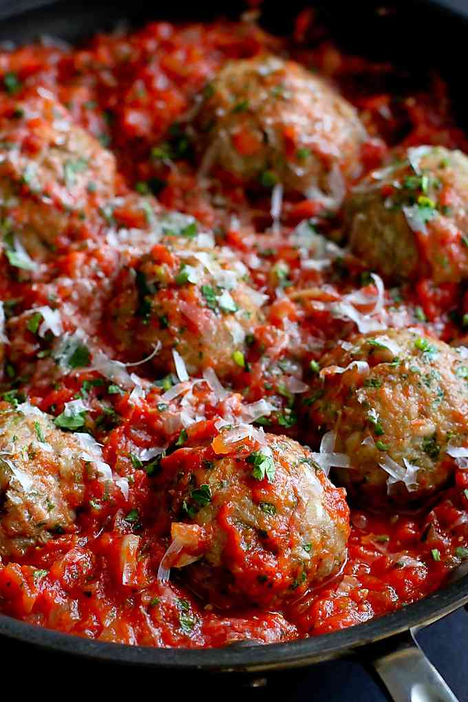 Big ground turkey meatballs and tomato sauce in a skillet.