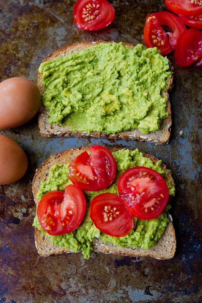 Avocado toast being assembled, with sliced tomatoes and eggs.