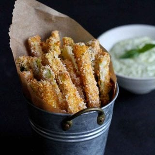 Baked zucchini fries in a metal container, yogurt dip in the background.