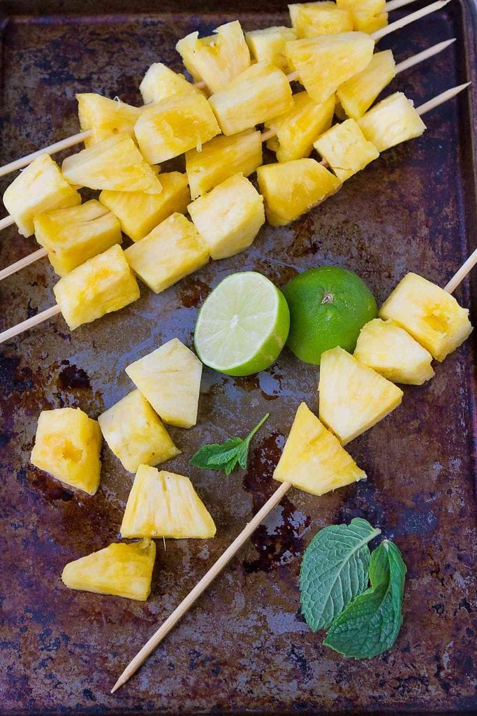Pineapple pieces on a baking sheet, being threaded onto wooden skewers. Ready for grilling!