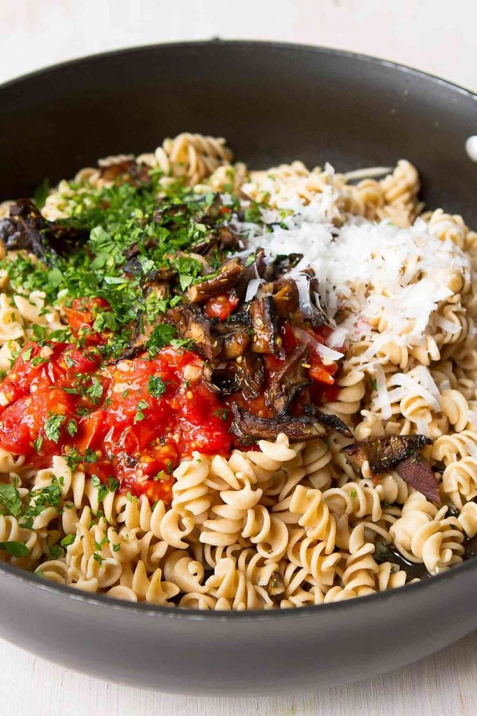Whole wheat pasta, roasted tomatoes, roasted mushrooms and Parmesan cheese in a skillet.