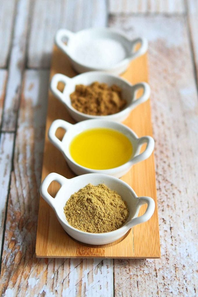 Ground cumin, coriander, olive oil and salt in small dishes.