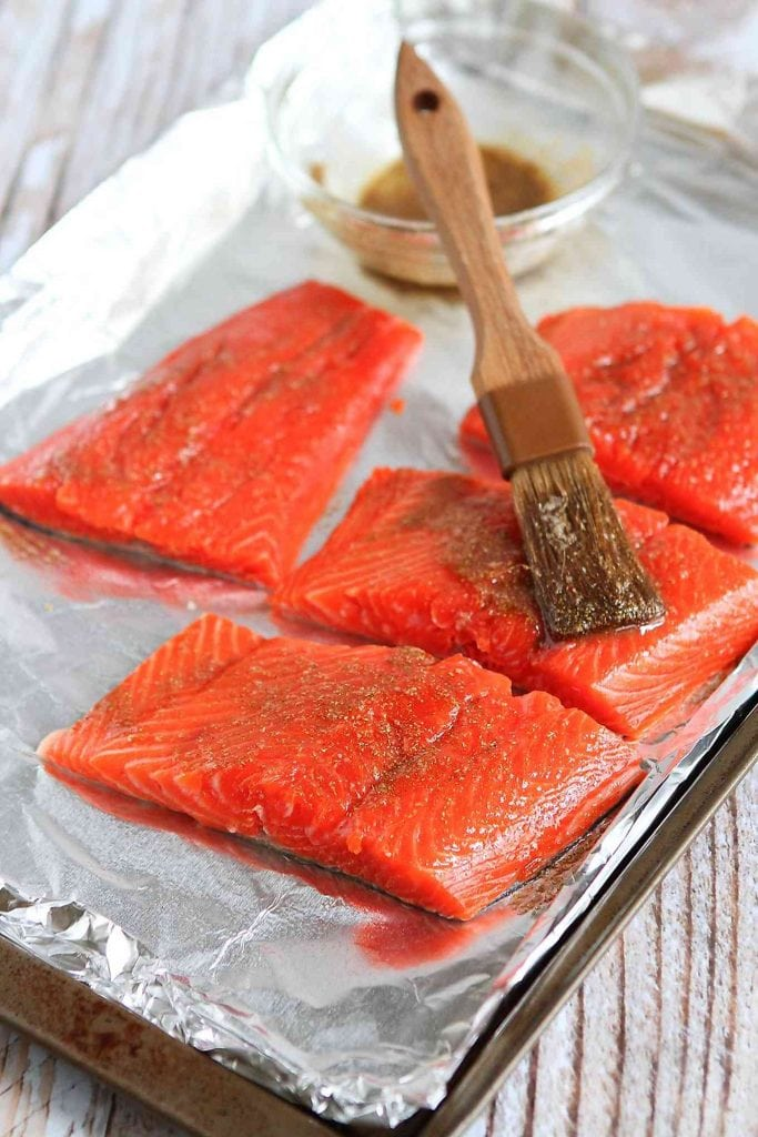 Salmon fillets on a baking sheet, rubbed with spices and being brushed with a honey mixture.