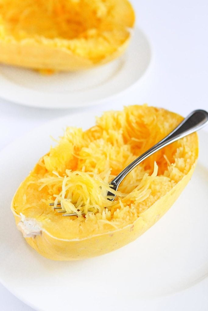 Cooked spaghetti squash half, twirling the strands out with a fork.