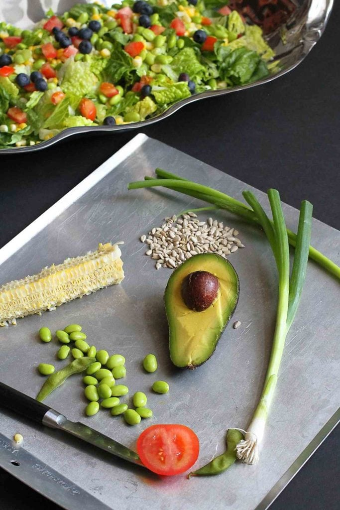Ingredients for summer salad on a baking sheet. Avocado, edamame, tomato and corn.