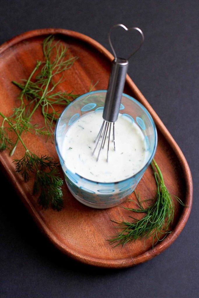 Light dill buttermilk dressing with a whisk, sitting on a wooden plate.