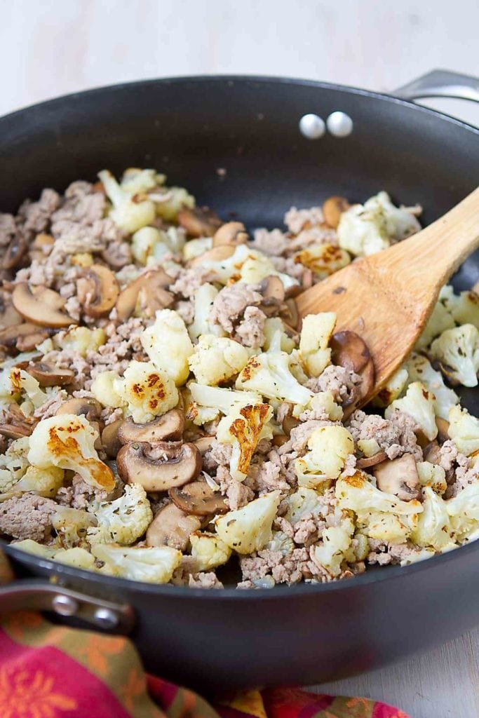 Ground turkey, roasted cauliflower and sauteed mushrooms in a large skillet.