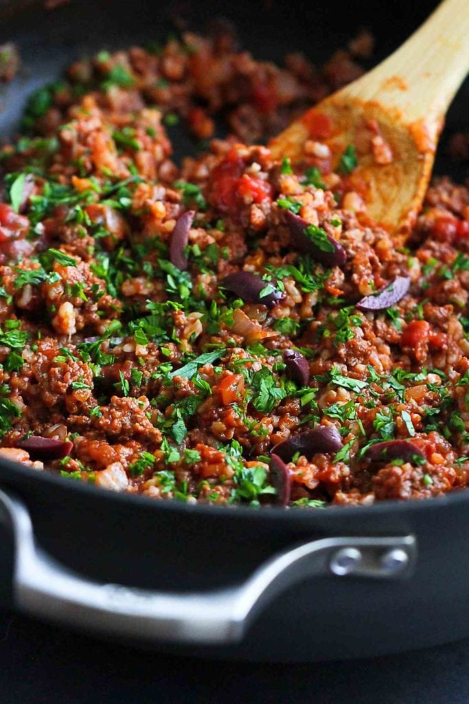Ground peppers, tomatoes, parsley and rice in a skillet. The filling for Greek stuffed peppers.