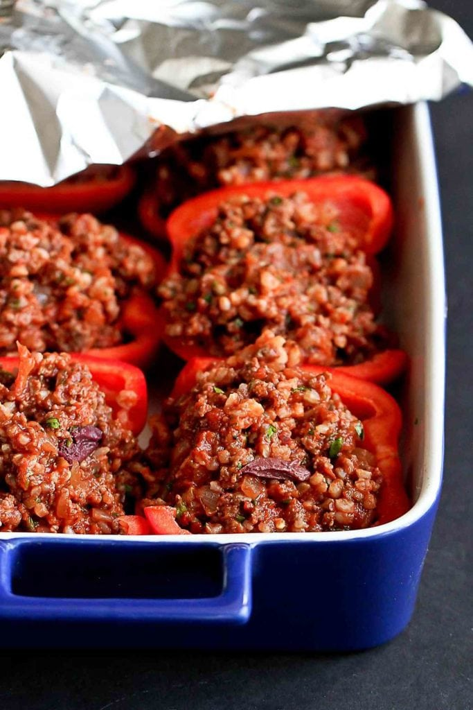 Stuffed red bell peppers in a baking dish, ready for the oven.