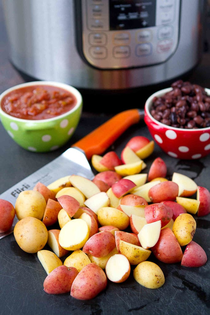 Halved Creamer potatoes on cutting board, with salsa, black beans and an Instant Pot pressure cooker.