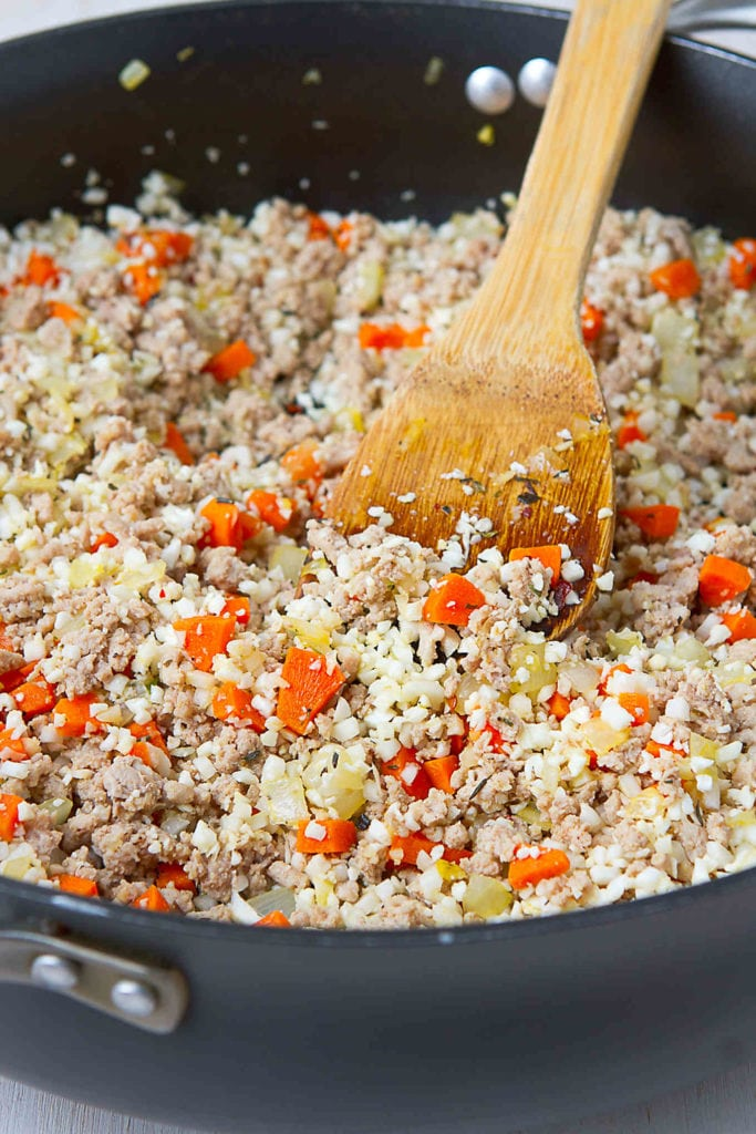 Cauliflower rice sauteed with vegetables and ground turkey in a large skillet.