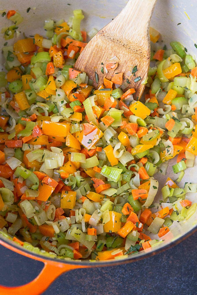 Sauteed leek, carrots, celery in herbs in a large saucepan.